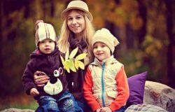 אמה ושני בניה לבושים בבגדי חורף בפארק